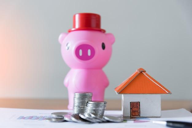 Pilha de moedas com caixa de dinheiro de porco e casa de papel na mesa de madeira