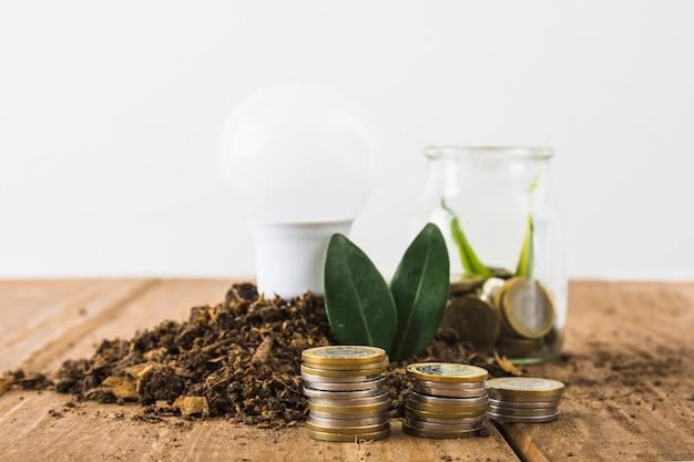 Pilha de moedas com lâmpada e jar