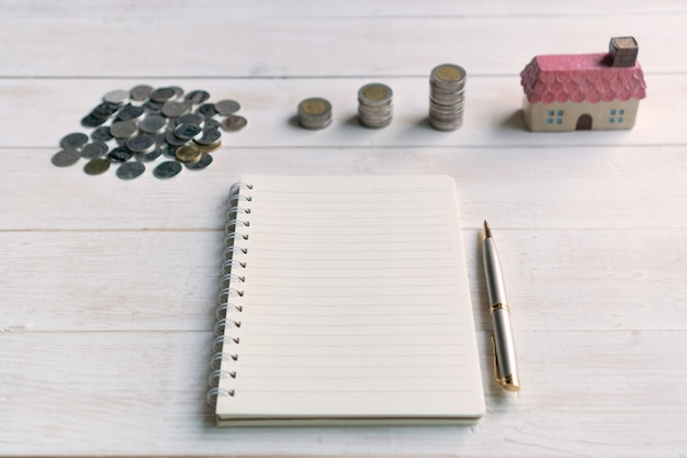 Pilha de moedas com modelo de casa e notebook para espaço de cópia, planos de poupança para o conceito financeiro de habitação, close-up