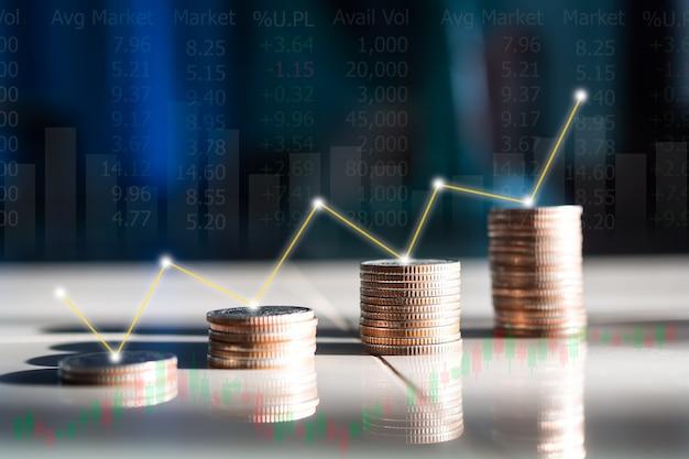 Pilha de moedas com o mercado de ações graph no fundo desfocado