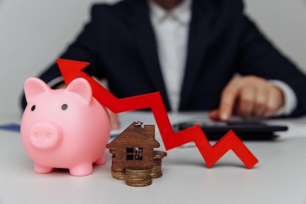Pilha de moedas com seta vermelha e cofrinho. ideias de investimento empresarial. conceito de investimento imobiliário.