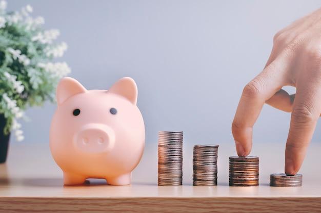 Pilha de moedas com um cofrinho de porco em um piso de madeira de manhã em casa, o conceito de economizar dinheiro para investimentos.