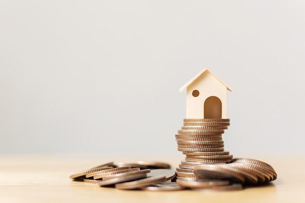 Pilha de moedas de dinheiro com casa de madeira