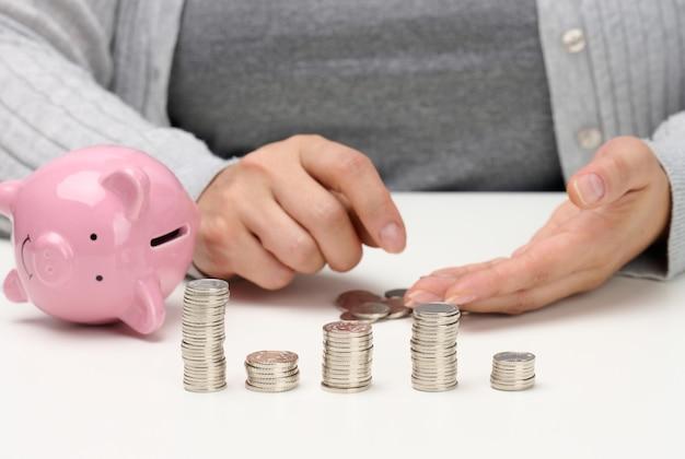 Pilha de moedas de metal e um cofrinho rosa de cerâmica. homem contando dinheiro, conceito de pobreza, planejamento orçamentário