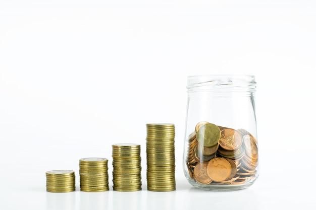 Pilha de moedas de ouro e um frasco de vidro de moedas de bronze no isolado