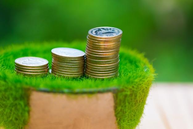 Pilha de moedas de ouro na grama artificial em pote