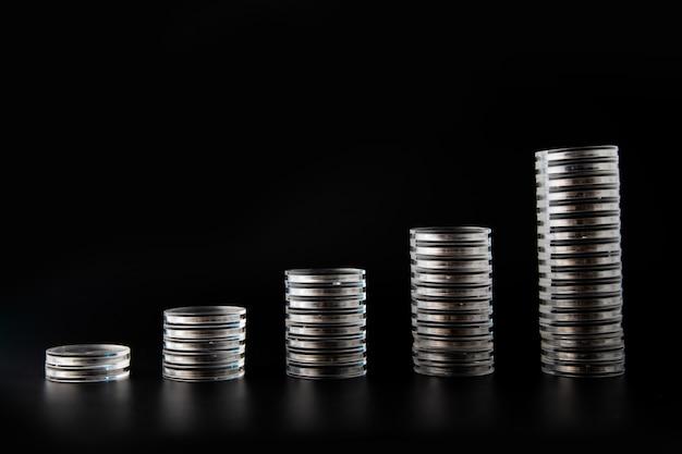 Pilha de moedas de prata com gráfico de crescimento isolada em fundo preto.