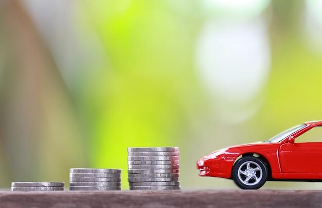 Pilha de moedas de prata com modelo de carro vermelho
