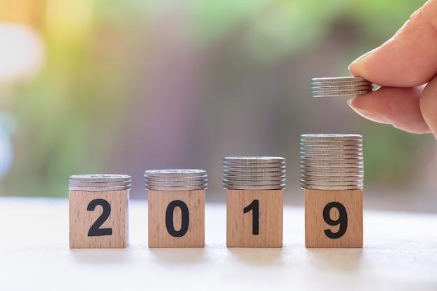 Pilha de moedas de prata no bloco de madeira número 2019 com mão de homem segurando e colocar a pilha de moedas no topo