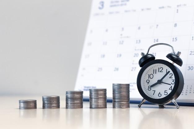 Pilha de moedas despertador e dinheiro com fundo de calendário