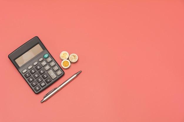 Pilha de moedas e calculadora com espaço de cópia.