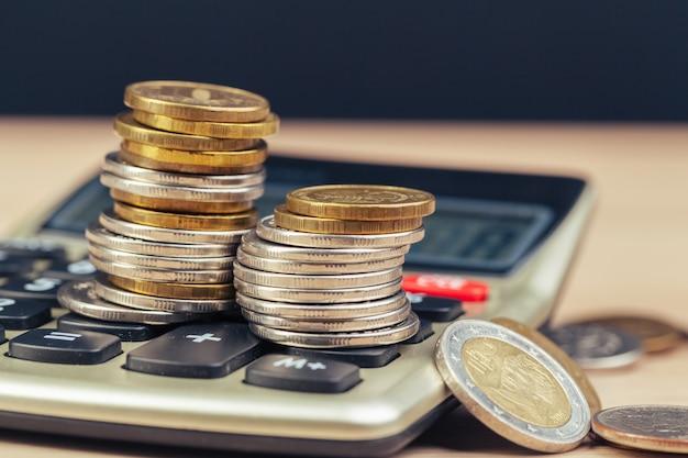 Pilha de moedas e calculadora, conceito para finanças de negócios