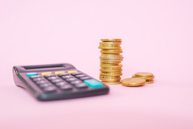 Pilha de moedas e calculadora em um fundo rosa. moedas de euro