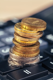 Pilha de moedas e calculadora, ideia de conceito para finanças empresariais