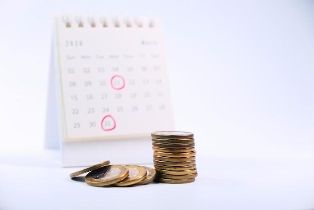 Pilha de moedas e calendário em fundo branco.