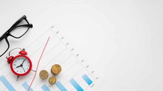 Pilha de moedas e despertador no topo do gráfico