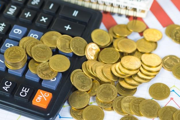 Pilha de moedas e folha de papel de gráfico financeiro com calculadora na mesa