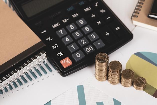 Pilha de moedas e folha de papel de gráfico financeiro com calculadora