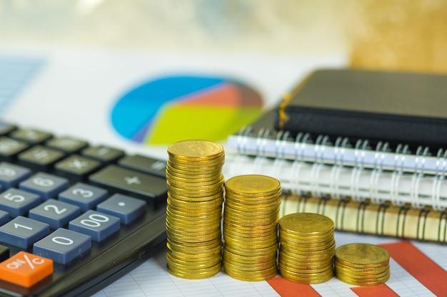 Pilha de moedas e folha de papel milimetrado financeira com calculadora