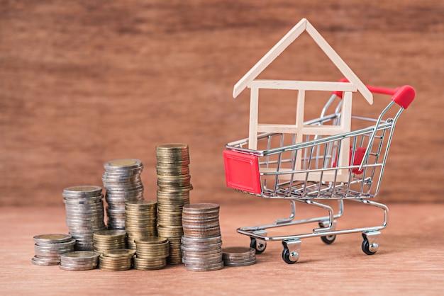 Pilha de moedas e modelo de casa de madeira no carrinho de compras em fundo de madeira marrom