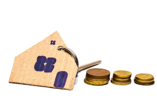 Pilha de moedas e modelo de madeira da casa, ideia de conceito para salvar e comprar casa.