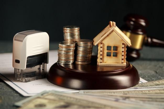 Pilha de moedas e um modelo de casa pequena