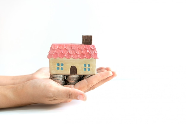 Pilha de moedas para poupar dinheiro e modelo de casa nas mãos, planos de poupança para habitação conceito financeiro, cópia espaço, close-up