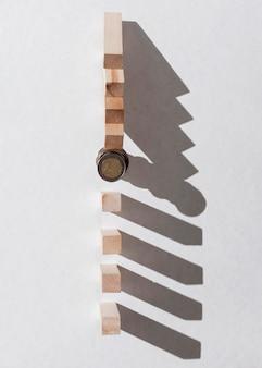 Pilha de moedas, parando as peças de madeira caídas vista superior