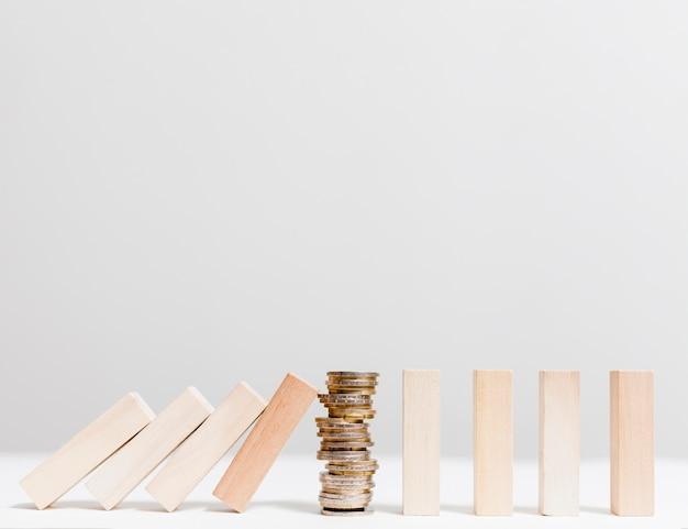 Pilha de moedas parando vista frontal de peças de madeira caídas