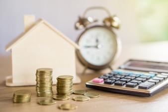 Pilha de moedas, relógio, modelo de casa e calculadora na mesa
