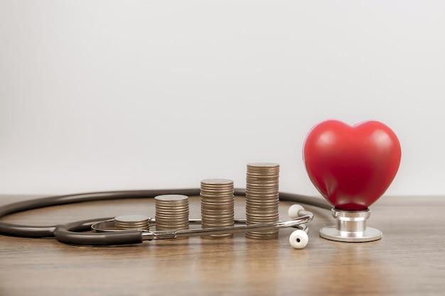 Pilha de moedas são empilhadas em forma de gráfico com balão de coração vermelho.