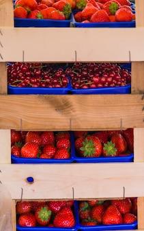 Pilha de morangos; cerejas na prateleira de madeira