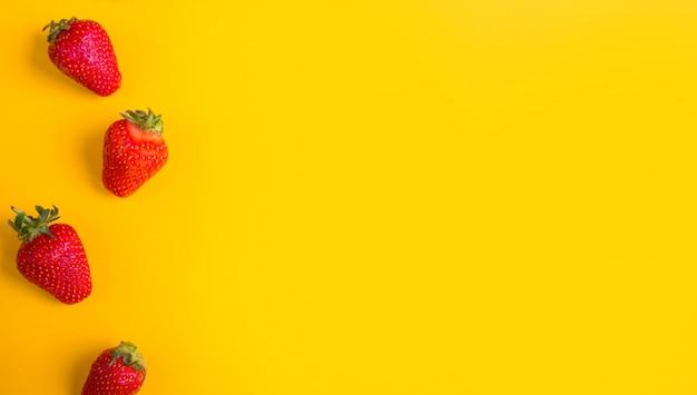 Pilha de morangos frescos em fundo amarelo.