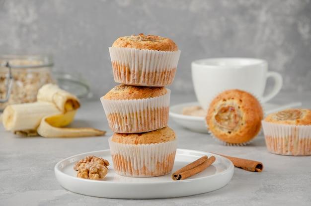 Pilha de muffins de banana com aveia, nozes e canela em um prato branco com uma banana e uma xícara