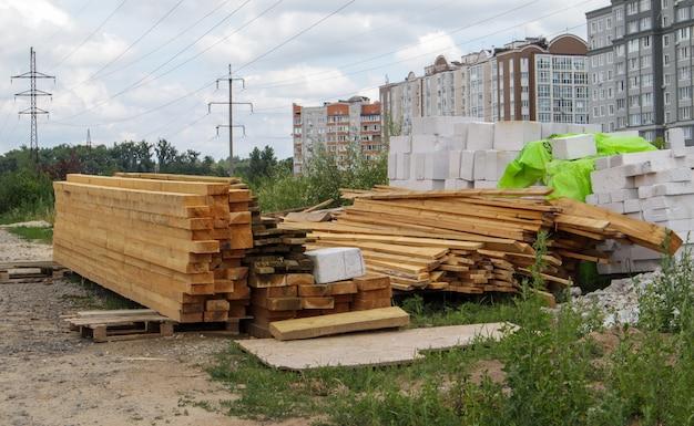 Pilha de muitas pranchas de madeira em um canteiro de obras, construção de plano de fundo do material. renovação, sobreposição de telhado, construção e conceito de casa. barras de madeira. materiais de construção.