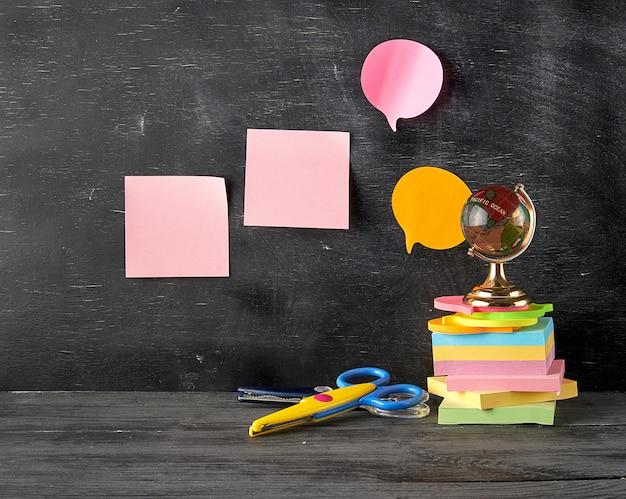 Pilha de multi adesivos pegajosos coloridos, globo de vidro, tesoura