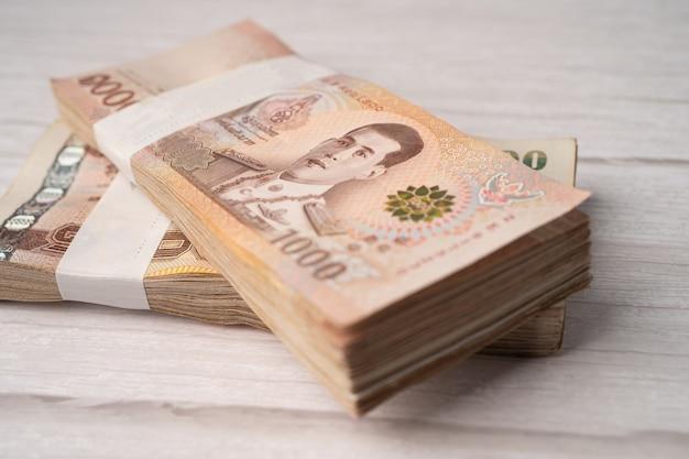 Pilha de notas de baht tailandês em fundo de madeira, conceito de investimento financeiro de economia de negócios.
