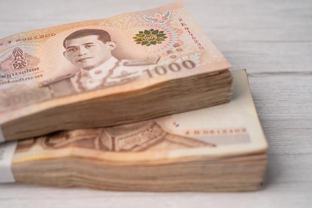 Pilha de notas de baht tailandês em fundo de madeira Foto Premium