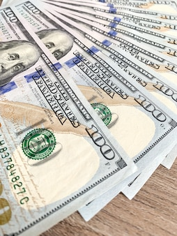 Pilha de notas de cem dólares na mesa de madeira