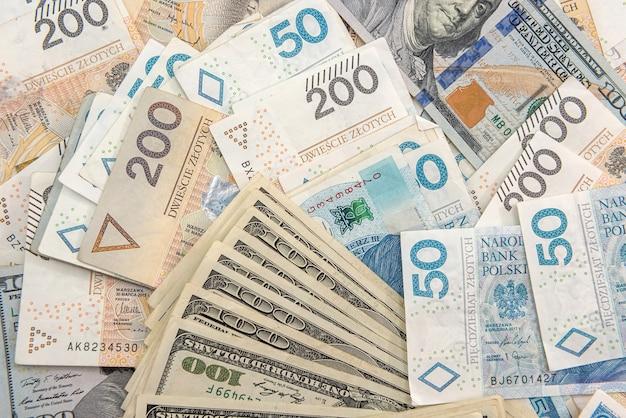 Pilha de notas de dólar americano e zloty polonês