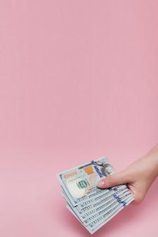 Pilha de notas de dólar na mão feminina em fundo rosa.