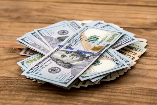 Pilha de notas de dólar na mesa de madeira