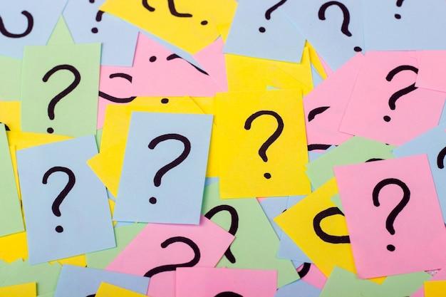 Pilha de notas de papel colorido com pontos de interrogação. fechar-se.