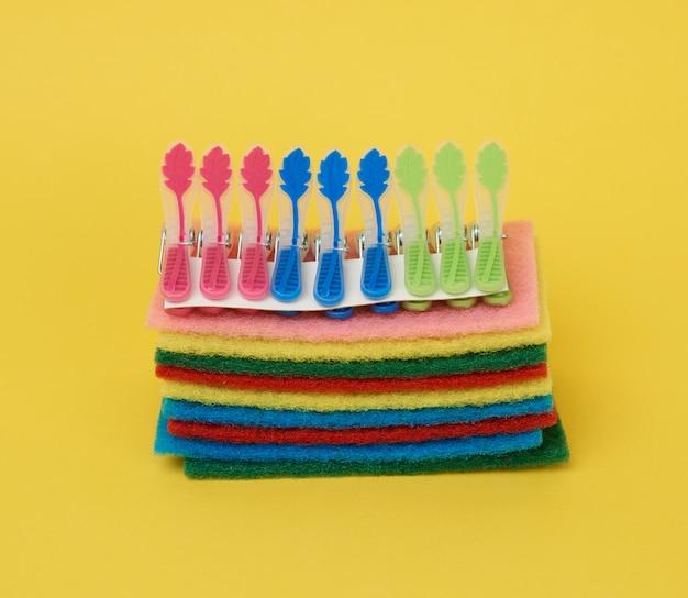 Pilha de novas esponjas de cozinha multicoloridas para lavar pratos e prendedores de roupa