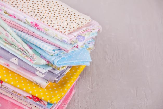 Pilha de novos tecidos em pano de cores diferentes na mesa
