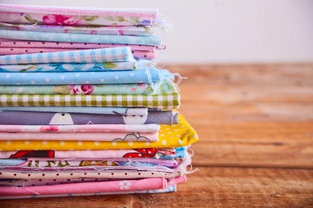 Pilha de novos tecidos em pano de cores diferentes sobre a mesa de madeira