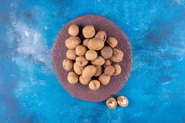 Pilha de nozes com casca na peça de madeira na mesa azul.