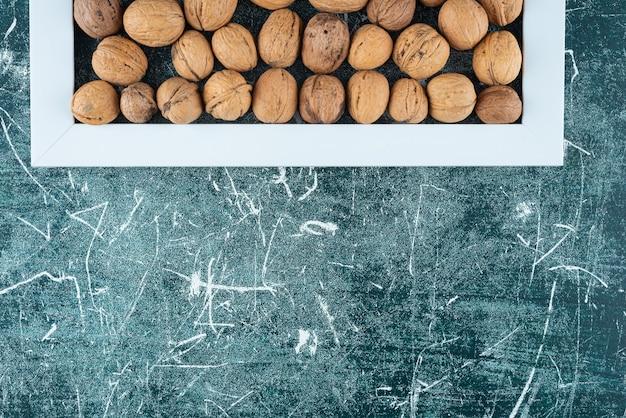 Pilha de nozes sem casca com moldura vazia na mesa de mármore.