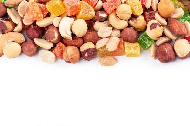 Pilha de nozes tostadas e frutas cristalizadas isoladas