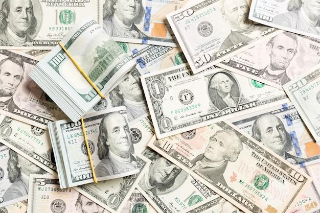 Pilha de pacotes de notas de dólar dos eua. notas de cem dólares com pilha de dinheiro no meio. fundo